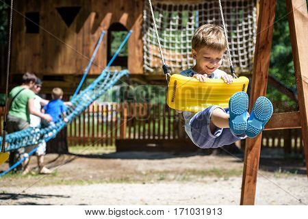 Summer, Childhood, Leisure, Friendship And People Concept - Happy Little Boy Swinging On Swing At Ch