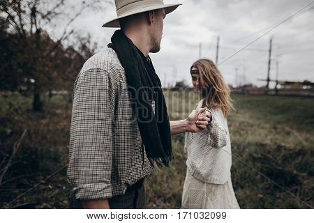 Stylish Hipster Couple Holding Sensually Hands. Boho Gypsy Woman And Man In Hat Embracing In Windy F