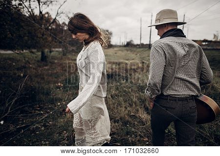 Stylish Hipster Couple Posing. Man In Hat With Guitar And His Boho Woman In Knitted Sweater In Windy