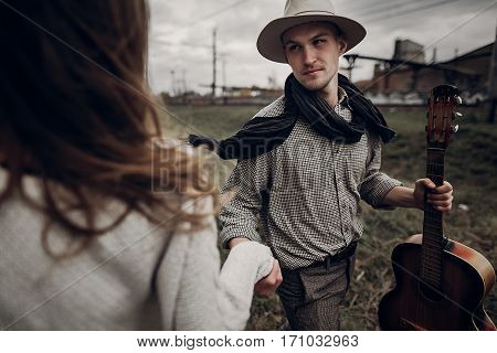 Man In Hat With Guitar Looking And Smiling To His Boho Woman In Windy Field. Atmospheric Sensual Mom