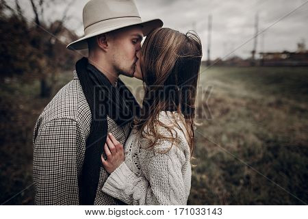 Boho Gypsy Woman And Man In Hat Kissing In Windy Field. Stylish Hipster Couple Hugging. Atmospheric