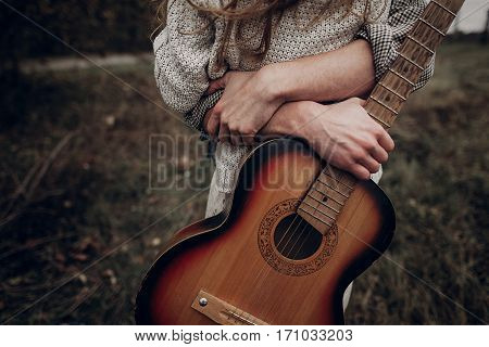 Man With Guitar Hugging His Boho Gypsy Woman In Windy Field. Atmospheric Sensual Moment. Stylish Hip