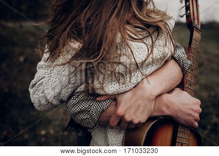 Man With Guitar Hugging His Boho Gypsy Woman Closeup In Windy Field. Atmospheric Sensual Moment. Sty