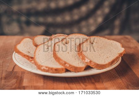 White bread on a wooden table. Top view. Fresh fragrant crispy sliced bread. Loaf of white bread slices on cutting board closeup. Home-made bread on an white porcelain plate.