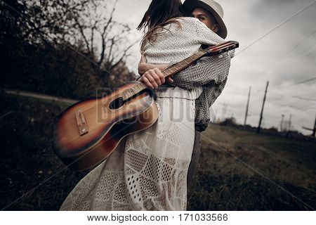 Man With Guitar Dancing With His Boho Gypsy Woman In Windy Field. Stylish Hipster Couple Hugging. At