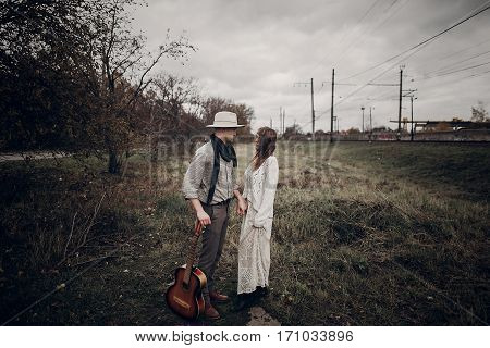 Stylish Hipster Couple Posing In Windy Field. Boho Gypsy Woman And Man With Guitar In Windy Field. A