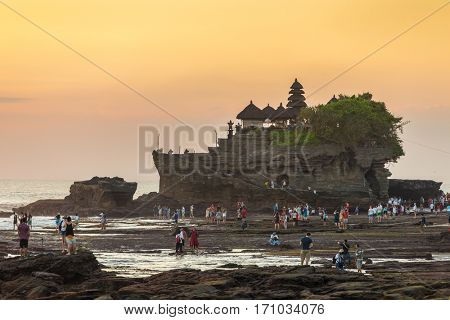 Bali, Indonesia - July 23, 2016: Tourists walk near the Tanah Lot temple during sunset in Bali, Indonesia