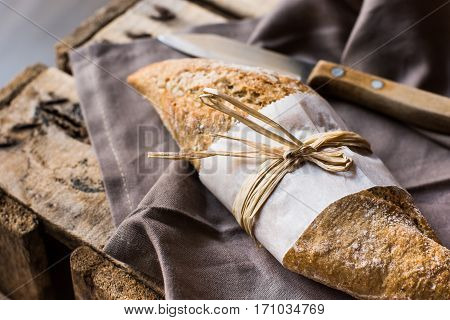 Loaf of rye whole wheat bread wrapped in parchment paper linen napkin knife vintage wood background top view selective focus poster