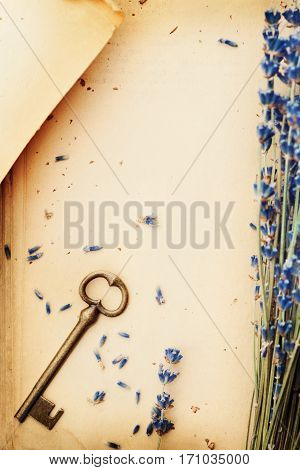 Retro still life with vintage paper key and lavender flowers nostalgic composition from above.