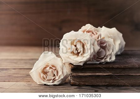 Retro still life with vintage rose flowers and ancient book. Nostalgic composition on old wooden table.