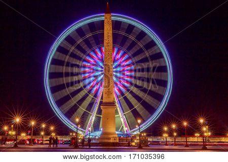 Ferris wheel and the Luxor Obelisk at the Place de la Concorde in Paris at night.