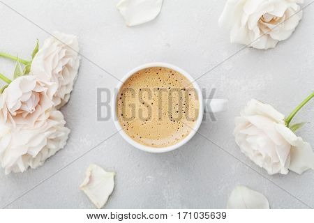 Coffee mug and vintage rose flowers for good morning on gray stone table from above in flat lay style. Beautiful breakfast on Mothers or Womans day.