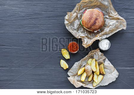 Fast food restaurant dish top view. Meat cheese burger in craft paper, potato chips and wedges. Take away set on dark black wood background. Hamburger and spicy tomato sauce.