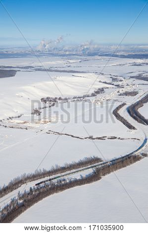 View from above freight train moving on snow covered plain from industrial chemical factory