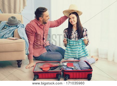 Young couple packing stuff into suitcase at home. Travel and vacation concept