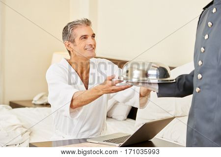 Room service bringing food to guest with laptop in a hotel room