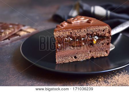 Piece Of Chocolate Sacher Torte On A Black Plate On A Slate,stone Or Metal Background.