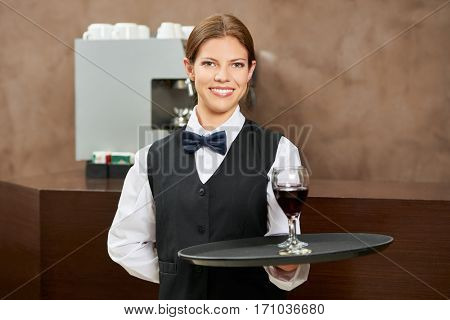 Waitress serving red wine on a tablet in a hotel restaurant