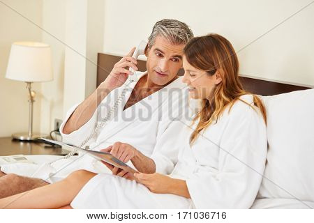 Couple with menu calling room service for food from hotel room