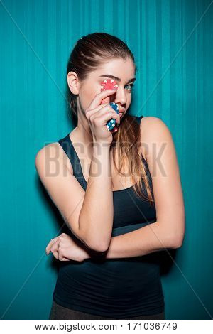 Young girl holding poker chips on blue studio background