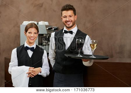 Waiter and waitress serving drinks in a hotel restaurant