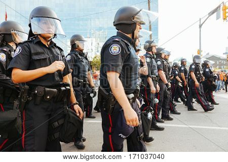 TORONTO, CANDA - JUNE 25, 2010: Police officers advance in unison upon a group of protestors during the G20 summit