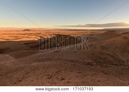 Panoramic view at sunrise over a stone desert in Morocco with the snowy Atlas mountains in the background and some clouds in the sky.