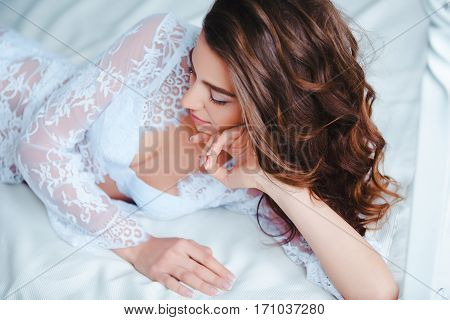 Awakening. Portrait of beautiful young woman with waking up in the morning. Beauty female wearing lingerie in bed.