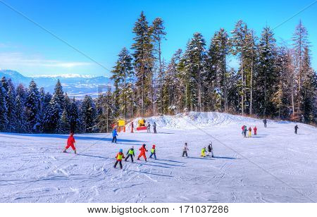 People in vacation practicing ski sport and snowboarding outdoor, in a famous place of Poiana Brasov - Romania