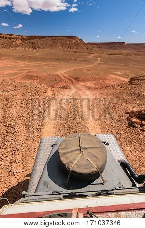 View from the top of a four by four oldtimer off-road vehicle driving off-road in a desert in Morocco. You can see the hood with the spare wheel in the foreground and some mountains in the background.