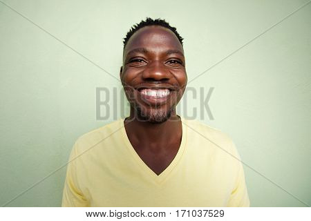 Funny Young African Man Smiling Against Green Wall
