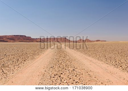 A dusty, empty off-road track in a stone desert in Morocco leading to the horizon and some small mountains.