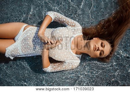 Girl in white transparent dress and bikini lies in sea water top view. Photographed close up.