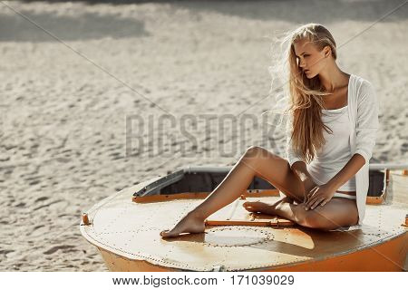 Girl sits on boat on sandy beach background. She lighted bright sun.
