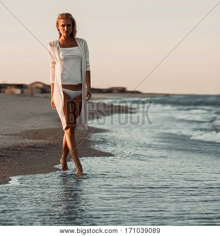 Girl in white tee-shirt and bikini on sea background. She walks along surf line.