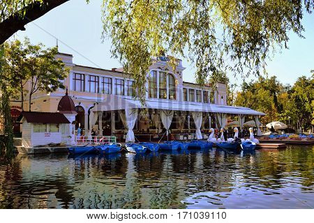 CLUJ-NAPOCA ROMANIA - SEPTEMBER 03 2012: Chios Casino restaurant and terrace near the lake in central park. People rent pedal boats and wooden boats.