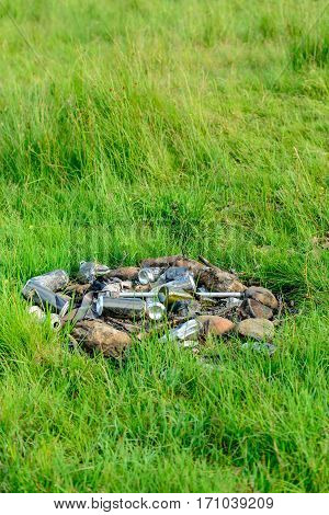 An abandoned camp fire and rubbish left in a rural location by inconsiderate campers.