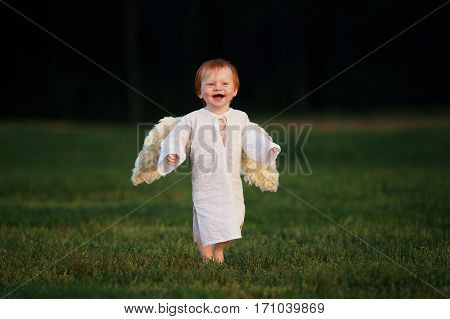 Angel sitting on grass and looking forward
