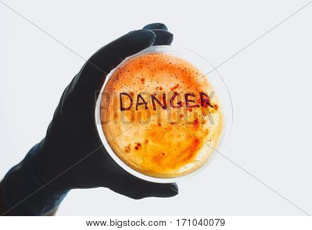 Word danger on Petri dish with bacterial infection test sample. Medical test for dangerous intestinal infectious disease. Contaminated water food concept. Disease outbreak control prevention biohazard