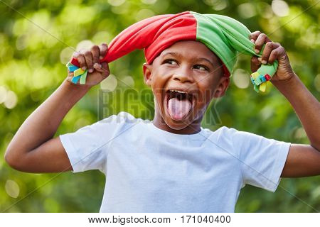 Child as court fool having fun showing his tongue
