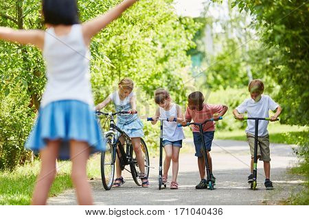 Group of kids ready for competition in the park with bike and scooters