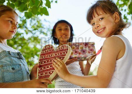 Children wish happy birthday to girl with gift