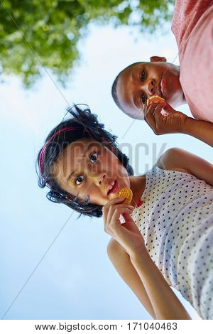 Children nibble cookies together in summer