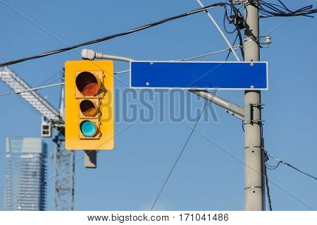 Yellow traffic light on the post and an empty road street sign with place for words
