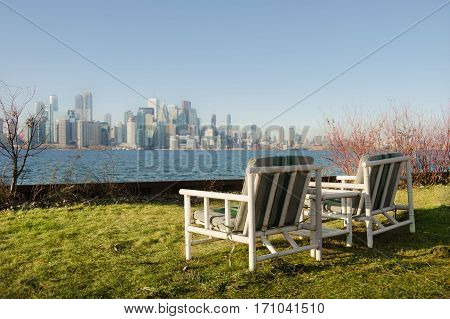 Two chairs on green grass with view of the metropolis
