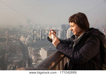 woman taking a selfie from the rooftop of St Paul's Cathedral on a foggy day in London, UK - city break - tourism concept