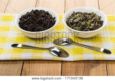 Bowls With Dry Green And Black Tea, Teaspoons On Napkin