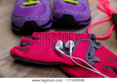 Fitness gym equipment. Sneakers with skipping rope. Workout gloves and footwear. Sport trainers and music headphones.