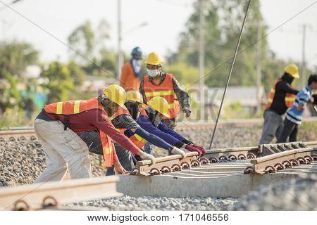 Construction team work in standard construction safety uniform installing precast concrete railway in mega project construction site