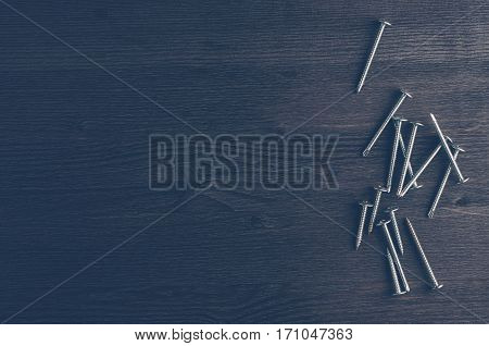 Old Screws On A Dark Wooden Background. Top View